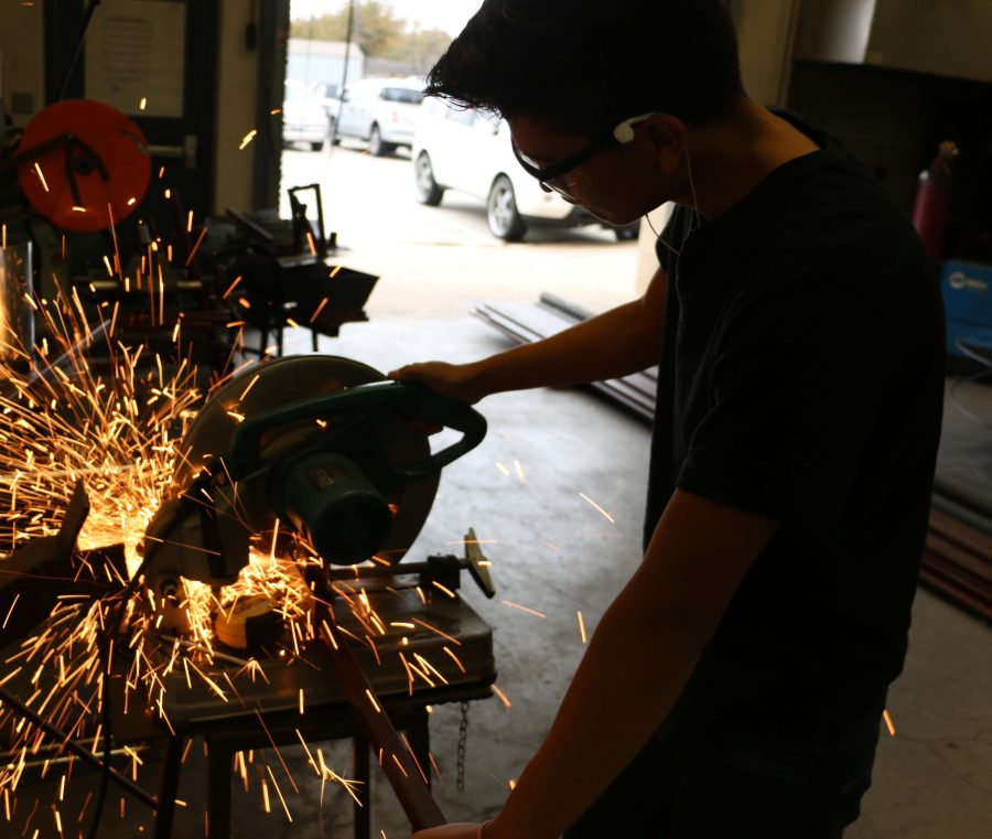 Junior Ismael Chavez cuts a metal bar in pieces for a class project. Photo by junior Diego Perez.