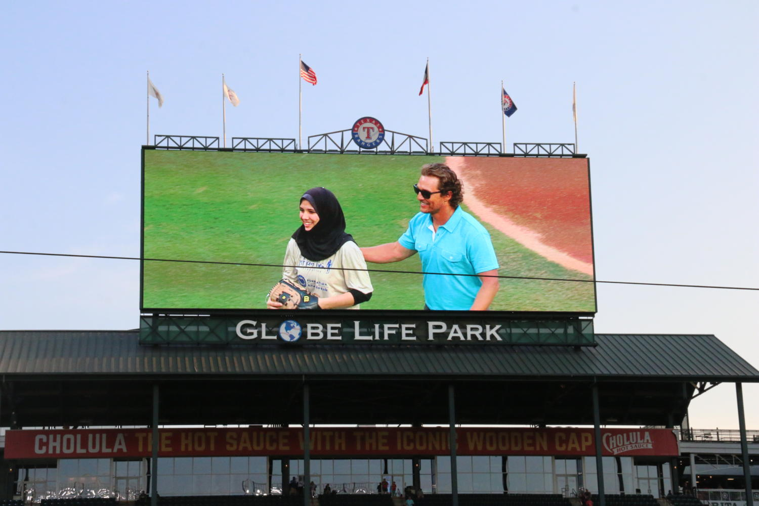 Senior Samiya Mohamed-Fawzy stands with actor Matthew McConaughey on the pitching mound before her pitch.