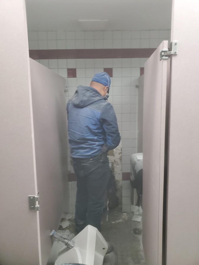 AISD maintenance drills into one wall to repair a pipe leak in the girls restroom on the 500 hallway next to Office 510.